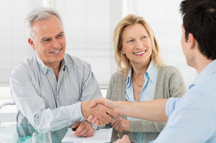 Senior couple shaking hands with fiduciary